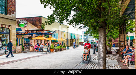 ASHEVILLE, NC, USA-27 JULY 19 : Wall Street in downtown is busy on summer day, with small crowds at cafe tables, while man pushes woman in wheelchair. - Stock Photo