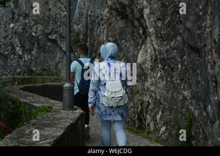 Muslim romantic couple traveling and exploring natural landscapes. Captured from behind. - Stock Photo