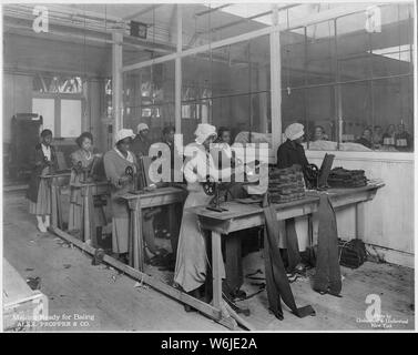 Manufacturing spiral puttees at plant of Alexander Propper & Company, New York City. Preparing the puttees for bailing. [African-American women working.] - Stock Photo