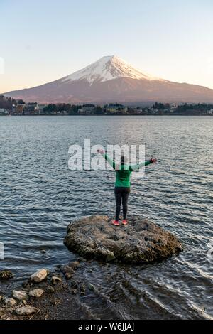 Evening atmosphere, young woman standing on a stone in the water and stretching arms into the air, view over Lake Kawaguchi, back of volcano Mt. - Stock Photo