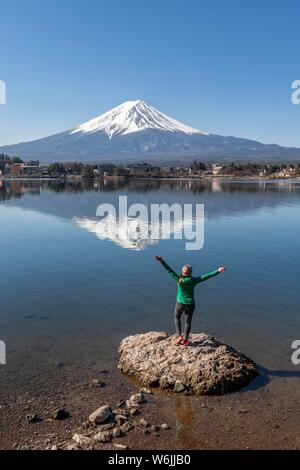 Young woman stands on stone in the water and stretches arms into the air, Lake Kawaguchi, back volcano Mt. Fuji, Yamanashi Prefecture, Japan - Stock Photo