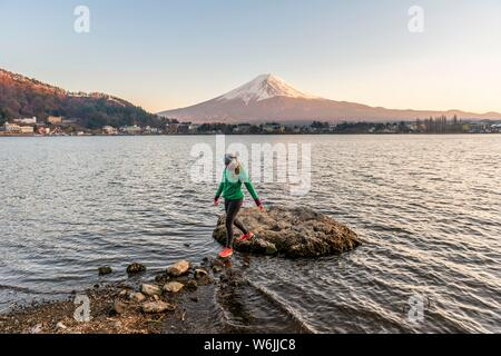 Evening mood, Young woman walks over stones in the water, view over Lake Kawaguchi, back volcano Mt. Fuji, Yamanashi Prefecture, Japan - Stock Photo