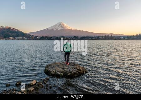 Evening mood, Young woman standing on a stone in the water and looking into the distance, view over Lake Kawaguchi, back volcano Mt. Fuji, Yamanashi - Stock Photo