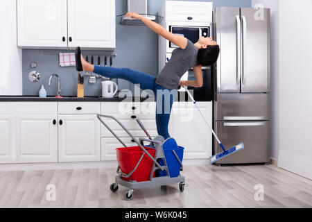 Close-up Of A Young Woman Slipping While Mopping Floor In The Kitchen - Stock Photo