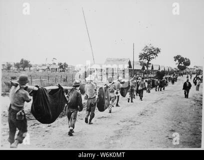 Photograph of American Prisoners Using Improvised Litters to Carry Comrades, 05/1942; Scope and content:  Original caption: This picture, captured from the Japanese, shows American prisoners using improvised litters to carry those of their comrades who, from the lack of food or water on the march from Bataan, fell along the road. Philippines, May 1942. General notes:  According to Colonel Melvin H. Rosen (U.S. Army Retired), this image is not a photograph taken during the Bataan Death March, but rather a photograph of a burial detail at Camp O'Donnell, the terminus of the Death March.  Mr. Ros - Stock Photo