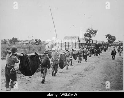Photograph of American Prisoners Using Improvised Litters to Carry Comrades; Scope and content:  Original caption: This picture, captured from the Japanese, shows American prisoners using improvised litters to carry those of their comrades who, from the lack of food or water on the march from Bataan, fell along the road. Philippines, May 1942. General notes:  According to Colonel Melvin H. Rosen (U.S. Army Retired), this image is not a photograph taken during the Bataan Death March, but rather a photograph of a burial detail at Camp O'Donnell, the terminus of the Death March.  Mr. Rosen is a s - Stock Photo