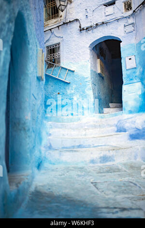 Stunning view of a narrow alleyway with the striking, blue-washed buildings. Chefchaouen, or Chaouen, is a city in the Rif Mountains of Morocco.
