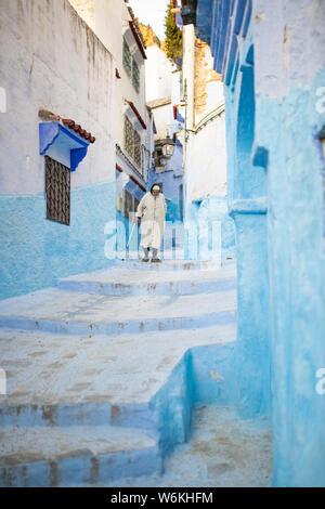 A Moroccan old man, wearing the traditional Djellabah is walking through the narrow alleyway of Chefchaouen, Morocco.