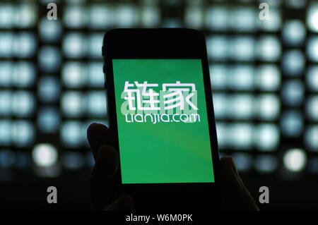 --FILE--A Chinese mobile phone user uses the app of Chinese real estate agency Lianjia, also known as Homelink, on his smartphone in Ji'nan city, east - Stock Photo