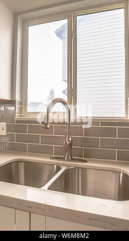Vertical Double bowl stainless steel sink against tiled wall with window and cabinets - Stock Photo