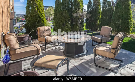 Panorama Upholstered metal chairs and round table at the patio of a home under blue sky - Stock Photo