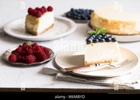 Slice Of Classical New York Cheesecake with blueberries and raspberries On White Plate. Closeup View. Home bakery concept/ - Stock Photo