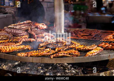 meat grilled outdoors  on the embers in local holidays - Stock Photo