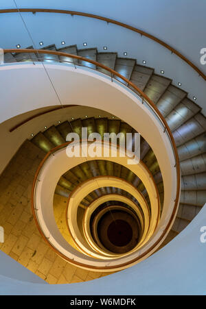 Spiral Staircase Leads Down Several Floors With Dramatic Lighting. - Stock Photo