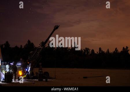 Soldiers assigned to the 1st Battalion, 258th Field Artillery of the New York Army National Guard conduct night fire training with the M-777A2 howtizer at Fort Drum, New York during their annual training on July 30, 2019. ( U.S. Army National Guard photo by Sgt. Matthew Gunther) - Stock Photo