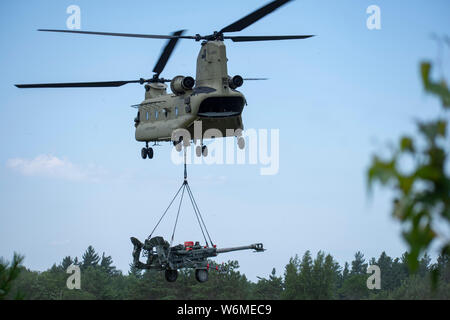 A C H-47 flown by Soldiers assigned to the New York Army National Guard's Bravo Company, 3rd Battalion, 126th Aviation carries an M-777A2 howitzer to a firing site during sling load training conducted with the 1st Battalion, 258th Field Artillery at Fort Drum on July 27, 2019. The 1st Battalion, 258th Field Artillery Soldiers were conducting live fire training and other exercises at Fort Drum as part of their two week annual training. ( U.S. Army National Guard photo by Sgt. Matthew Gunther) - Stock Photo