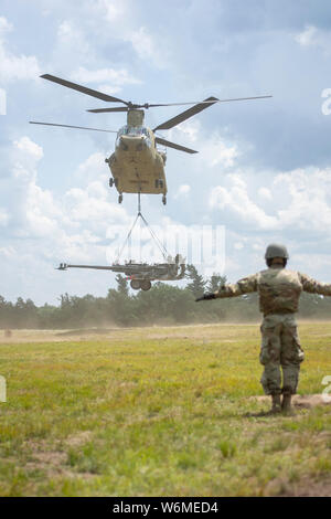 A Ch-47 flown by the New York Army National Guard's Bravo Company, 3rd Battalion, 126th Aviation takes off with an M-777A2 howitzer during sling load training sast Fort Drum, N.Y. on July 27, 2019. The 1st Battalion, 258th Field Artillery Soldiers were conducting live fire training and other exercises at Fort Drum as part of their two week annual training. ( U.S. Army National Guard photo by Sgt. Matthew Gunther) - Stock Photo