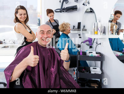 Portrait of happy bald man sitting in barber chair after haircut, giving thumbs up - Stock Photo