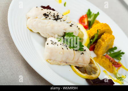 Recipe of dietary steamed merluse with vegetables: 250g of cod-like fish steam in pan with water and olive oil for 10 minutes, season with salt and pe - Stock Photo