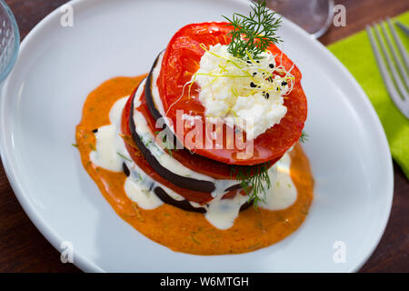 Grilled slices of eggplant and tomatoes in stack with spicy sauce - Stock Photo