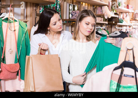 Young smiling female friends choosing fashion green pullover in the boutique - Stock Photo