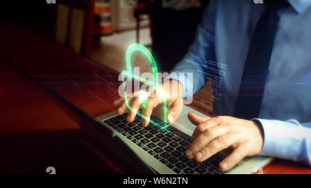 Man typing on laptop with padlock hologram screen over keyboard. Cyber security, computer protection and internet safety concept. - Stock Photo