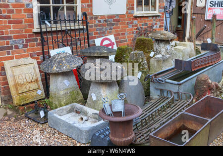 Staddle stones and vintage stone garden ornaments on display in the yard of an antique shop in Hungerford, a historic market town in Berkshire, UK