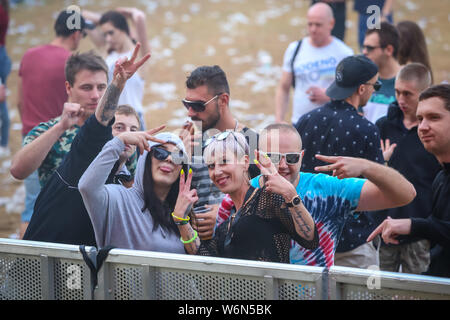 Brezje, Croatia - 20th July, 2019 : Audience posing with hands up in the morning of the Forestland, ultimate forest electronic music festival located - Stock Photo