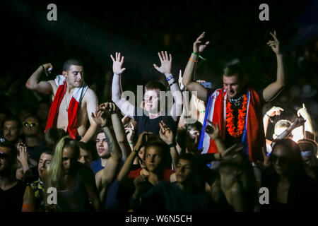 Brezje, Croatia - 20th July, 2019 : Audience dancing with hands up during the Forestland, ultimate forest electronic music festival located in Brezje, - Stock Photo