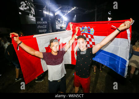 Brezje, Croatia - 20th July, 2019 : Two guys with a Canadian and Croatian flag posing on the Forestland, ultimate forest electronic music festival loc - Stock Photo