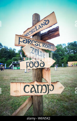 Brezje, Croatia - 20th July, 2019 : Wooden signs with different directions on the Forestland, ultimate forest electronic music festival located in Bre - Stock Photo