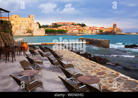 Panorama of picturesque colorful Collioure through bay from restaurant in spring day - Stock Photo