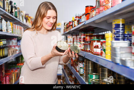 Cheerful positive smiling woman customer holding canned fish  goods in the food store - Stock Photo