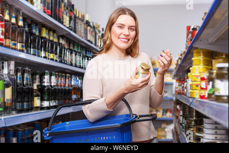 Portrait of woman choosing preserved goods in the food store - Stock Photo