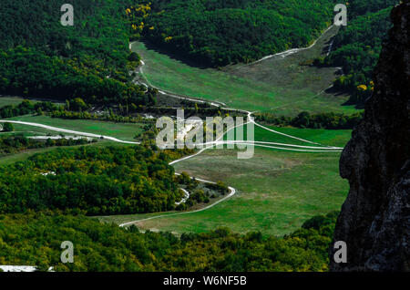 Serpentine mountain roads on white sand among the forest. Aerial view - Stock Photo