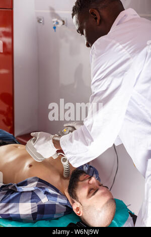 Rescue team making defibrillation to patient in ambulance car - Stock Photo