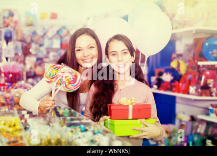 Portrait of smiling mother and daughter holding gifts and balloons in toys store - Stock Photo