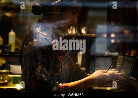 Melbourne, Australia-October 21,2018: Waitress of a restaurant charges in cash, seen from the street. - Stock Photo