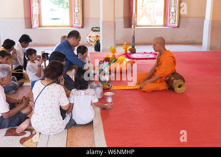 Phuket, Thailand, 04/19/2019 - Single buddhist monk praying with a family  at the Chalong Temple. - Stock Photo