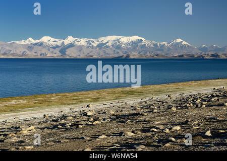The beautiful Karakul lake by the Pamir highway. View on the lake and Peak Lenin near Karakul village in the Pamirs, Tajikistan, Central Asia. - Stock Photo