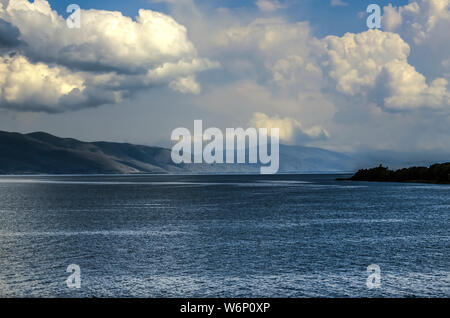 View of the sky, darkened by huge Cumulus clouds coming from the mountains and hanging over the mountain lake Sevan, located in the mountains of Armen - Stock Photo