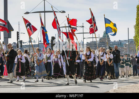 Norwegian patriots holding national flags and parade crowd in during Norways' independence day celebration events in Ostermalmstorg, suburb, Sweden - Stock Photo