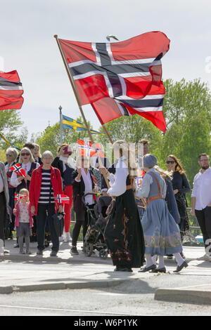 Norwegian patriotic women holding national flags and crowds looking on during their parade to celebrate Norway's independence day in Skansen, Sweden - Stock Photo