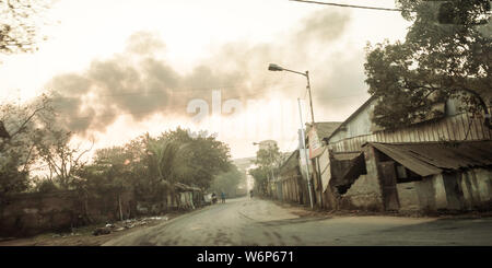 Kolkata, India - May 1, 2018 - Burning fire from garbage heap in industrial area, causing a large flame and smoke in the air over dramatic sky backgro - Stock Photo