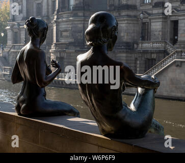 Two of the figures in the sculpture Drei Mädchen und ein Knabe by the River Spree, Berlin, Germany - Stock Photo