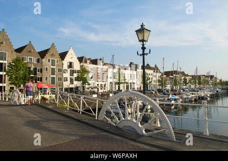 A couple walking the dog at the Kinderdijk and the Spijker Bridge with historic buildings in the city of Middelburg, the Netherlands - Stock Photo