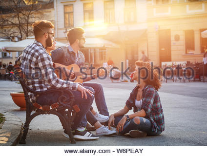 Group of people hangout at the city street.They sitting on bench ,singing and playing guitar. - Stock Photo