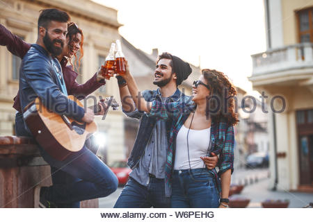 Group of young people hangout on street in downtown.They standing by the city square,drinking and playing guitar. - Stock Photo