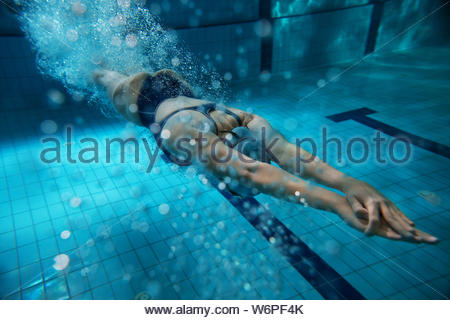 Swimmers at the swimming pool.Underwater photo - Stock Photo