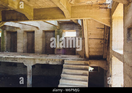 The destroyed big concrete building in a foggy haze. The remains of the frame of gray concrete piles and debris of the building structure. Background. - Stock Photo